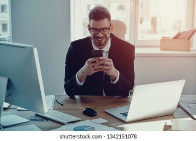 Great news. Handsome young man in formalwear using his smart phone and smiling while sitting in the office