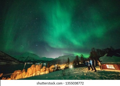great Northern lights in Tromsö Norway Lyngen fjord by a cabin green and pink lights like a angel