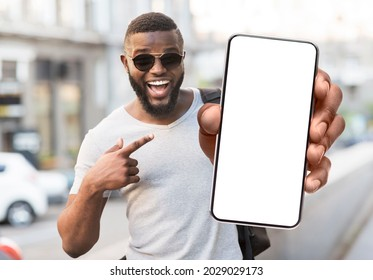 Great Offer. Portrait of excited black man standing outdoors holding big phone with white blank screen in hand, showing close to camera pointing at device. Gadget with empty free space for mock up