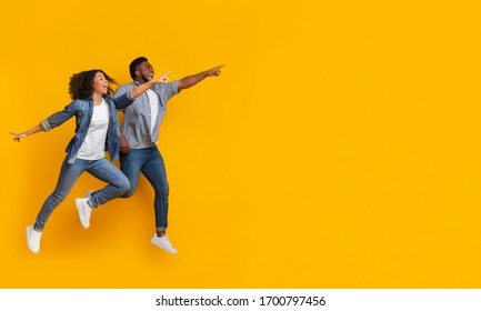 Great Offer. Positive black couple jumping in air and pointing at copy space on yellow background, panorama