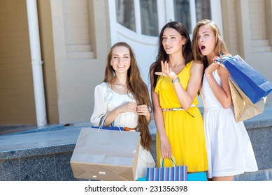 Great option in a shop. Three young and pretty girls are standing with shopping bags in front of the shop window and looking on a great sales offer