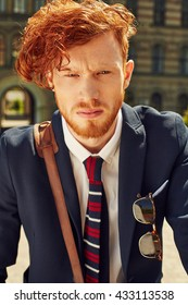 Great outdoor portrait of serious student with red hair and beard wearing necktie
