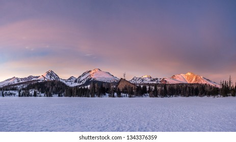 Great panorama view of High Tatras mountains captured from the frozen Strbske lake (Strbske pleso) during the magenta colorful sunset.