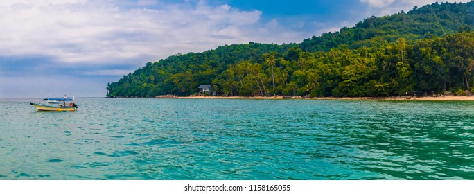A great panoramic view of Petani Beach on Perhentian Kecil Island in Malaysia. The anchored motor boat with the long stretch of golden sand and lush forest was taken from a floating platform.
