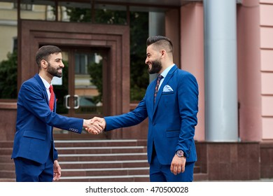 Great partnership. Portrait of a young Saudi businessman greeting his business partner with a handshake in front of the business center outdoors