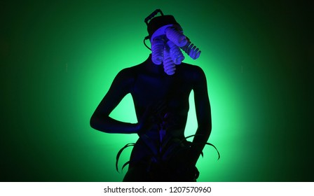Great photo of black mannequin, holding red potted flower, sitting in black noir atmosphere on green screen wall chroma key background. Ideal choise for different art projects, colages and posters