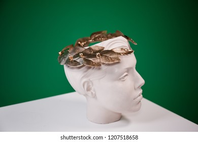 Great photo with golden art decoration wreath on white woman statue head. Awesome choise for art projects, colages and posters.