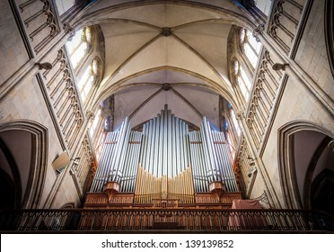 Great pipe organ under arched ceiling in old catholic church shining in sunlight. View from below. Largest musical instrument mostly used in church service in western countries.