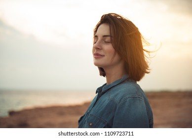 Great pleasure. Charming calm young woman is standing near sea with closed eyes and expressing delight. She is posing against wonderful sunset while enjoying last rays of the sun