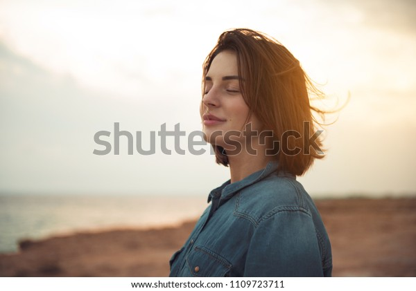 Großes Vergnügen. Charmante junge Frau steht in der Nähe des Meeres mit geschlossenen Augen und bringt Freude zum Ausdruck. Sie posiert gegen wunderschönen Sonnenuntergang und genießt die letzten Sonnenstrahlen