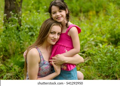 Great portrait of siblings with a lot of juicy green grass in the background. Two beautiful sisters embrace each other with spread smiles.