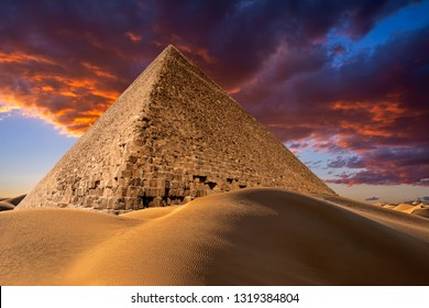 The Great Pyramid of Giza (also known as the Pyramid of Cheops) in desert dunes against the beautiful sunset sky with colorful clouds in Egypt