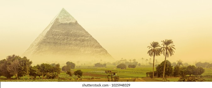 Great pyramid of Khafre in Egypt. Fantasy of egyptian landscape with ancient pyramid of Chephren in morning haze. Wide panorama in green oasis with fields and palm trees for your banner or header.