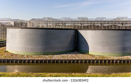 Great rain barrels of metal at a greenhouse in the Westland in the Netherlands.