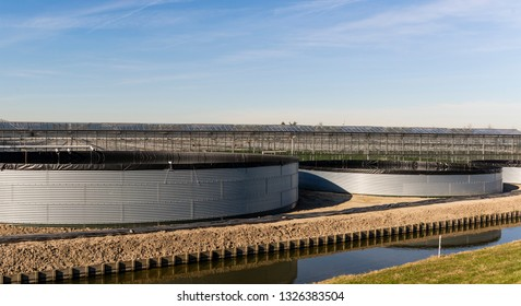 Great rain barrels of metal at a greenhouse in the Westland at Maasdijk in the Netherlands.
