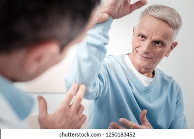 Great result. Delighted pensioner keeping smile on face while staring at medical worker