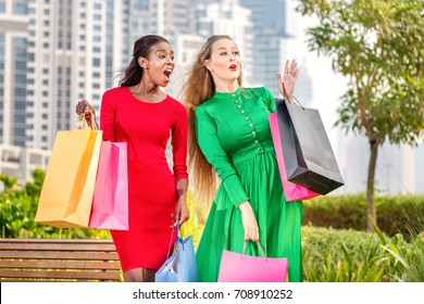 Great sale shopping. Two shopaholics surprised and holding shopping bags. Two young ladies doing shooping.
