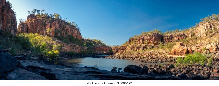 Great sandstone cliffs at Katherine River Gorge panorama in Nitmiluk National Park, Northern Territory, Australia. Location of the first stopover where the river is blocked by rocks and vegetation.