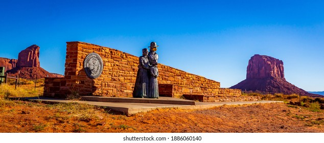 Great Seal of the Navajo Nation and Bronze Navajo Family Statue (with face mask) at the entrance of Monument Valley, which is closed due to COVID-19 pandemic.