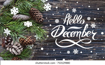 "Great season texture with winter mood. Spruce branches, cones and snowflakes on old wooden rustic background. Nature december background with hand lettering ""Hello December""."
