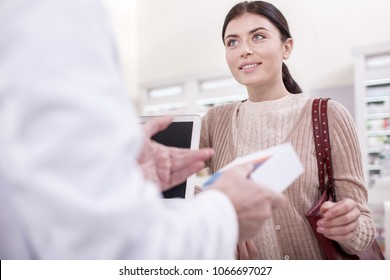 Great service. Low angle of charming nice female client smiling while consulting with salesman