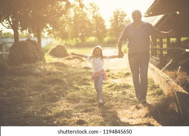 It's great to spend time at the farm. Granddaughter and grandfather on the farm together.  Copy space. Looking on the camera.