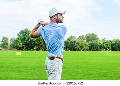 Great strike. Side view of confident golfer swinging his driver and looking away while standing on golf course