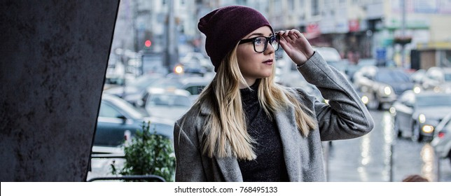 Great style. Panoramic view of stylish hipster girl holding glasses and looking away while standing outdoors and city street with cars on background. Young stylish woman in coat. Urban fashion concept
