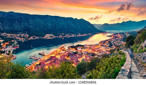 Great summer sunset in Kotor port. Aerial evening view of Kotor bay and Old Town from hill of  Lovcen Mountain. Beautiful world of Mediterranean countries. Traveling concept background.