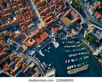 Great sunny cityscape of old Dubrovnik with houses with shingled roofs, churches, fortification walls and a pier with many yachts and boats. People are walking on streets. Top view horizontal photo.