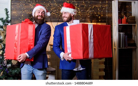 Great surprise. Prepare huge surprise gift. Men compete who has larger size. Bigger gift battle. Men santa carry big gift boxes. Size matters. Biggest gift for christmas. Big wrapped box with ribbon.