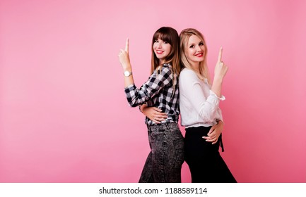 Great team, two successful colleagues  posing over pink background and  showing signs.