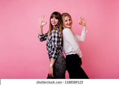 Great team, two successful colleagues  posing over pink background and  showing signs.  Lucky mood.
