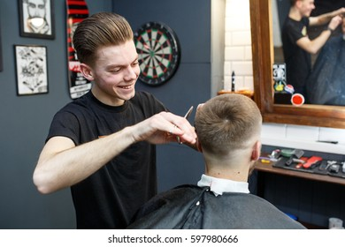 Great time at barbershop. Cheerful young bearded man getting haircut by hairdresser while sitting in chair at barbershop.