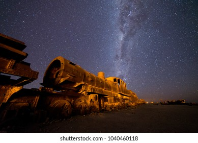 The Great Train Graveyard at Uyuni, Bolivia, where old steam locomotive trains rest under the incredible night sky.
