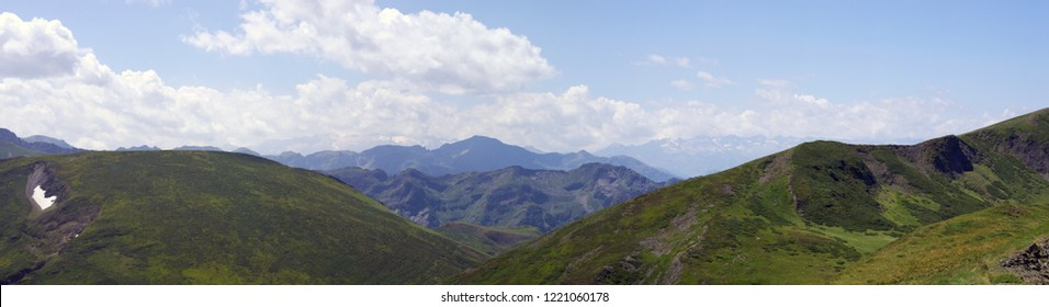 A great and typical view of the pyrenees mountains in Ariege, France, on summer. Looking towards luchonais and high range of Maladetta mounts. Summer pastures, grass, clouds and high tops.