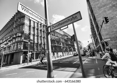 Great urban lifestyle view with wide street road, facades of modern buildings, sunny sky and pillar pointer in European city in black and white