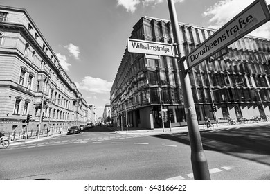 Great urban lifestyle view with wide street road, facades of old buildings, sunny sky and pillar pointer in European city in black and white