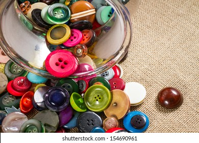 A great variety of colorful vintage buttons spilling out of a jar, against a fabric background. Landscape orientation.  Copy space.