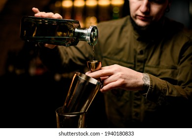 great view of bottle in hand of bartender from which he pours drink into polished steel jigger. Shaker cups in foreground