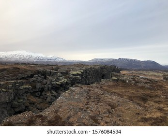 A great view of a mountain covered in snow in Iceland. You can also see a crack in the ground cause by a shift of tectonic plates.
