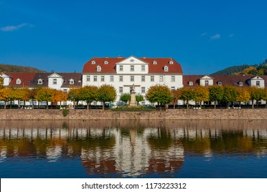 Great view of a row of baroque style houses & the Huguenot Museum in the middle, behind a linden tree grove & a monument of Landgrave Charles I; located at the harbour basin in Bad Karlshafen, Germany