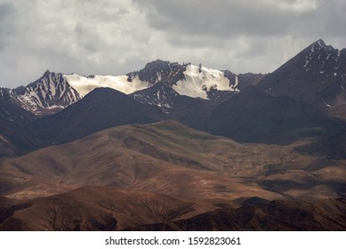 Great view of snow capped brown black mountain ranges and cloudscape of Kunlun mountains in Pamirs plateau in Xinjiang of China