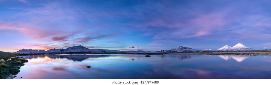 The great views of Lauca National Park landscape with its reflections over the Cotacotani Lagoons during a crescent moon cycle, on the right the amazing Payachatas: Pomerape and Parinacota Volcanoes
