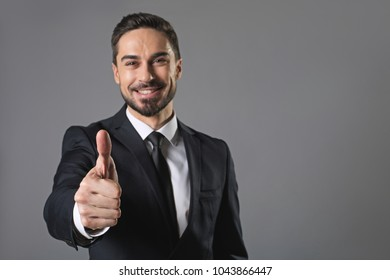 It is great. Waist up portrait of standing young smiling businessman showing ok sign. Isolated on grey background and focus on hand. Copy space in right side