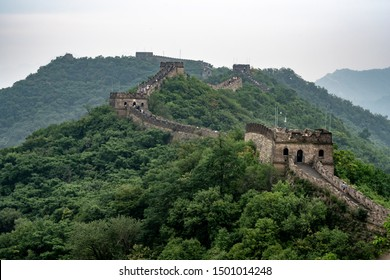 Great Wall in China. Panoramic view with green background and trees. Summer time with clouds and mist