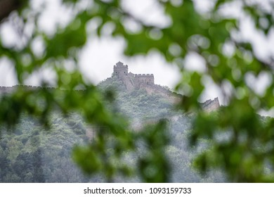 Great Wall of China seen through a blurred tree foreground