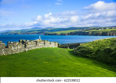 Great wall of Peel Castle constructed by vikings at Peel hill covered with green grass and beautiful coastline of Isle of Man in background