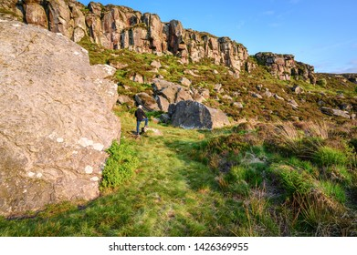 Great Wanney Crag and man to give perspective, on the edge of Northumberland National Park, a remote escarpment popular for rock climbing and walking