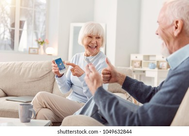 Great weather. Cheerful elderly couple sitting on the couch in the living room, checking the weather app and showing thumbs up, being happy about the weather
